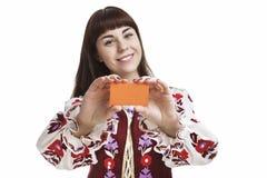 拿着和展示空插件的年轻白种人深色的女性 免版税图库摄影