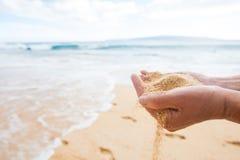 拿着和投下沙子的手在一个热带海洋海滩 免版税库存照片