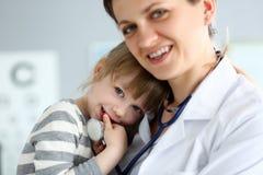 拿着和拥抱一点逗人喜爱的女孩患者的小儿科医生 库存图片