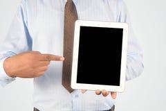 拿着和指向数字式片剂个人计算机的商人 库存照片