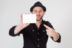 黑拿着和指向空插件的衬衣和黑帽会议的微笑的人 库存图片