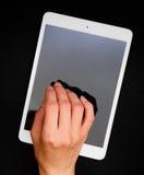 拿着和接触片剂个人计算机的手 免版税库存图片