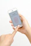 拿着和接触苹果计算机iPhone 5s颜色金子的妇女手显示指纹扫描接口 免版税图库摄影