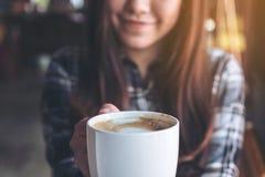 拿着和显示一个白色杯子的一名美丽的亚裔妇女的特写镜头图象,当喝与感到的热的咖啡好时 库存图片