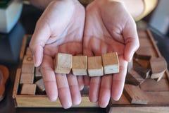 拿着和显示四个方形的木块的妇女的手 库存照片
