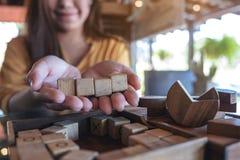 拿着和显示四个方形的木块的妇女 免版税库存照片