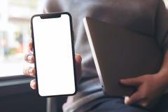 拿着和显示有空白的白色桌面屏幕的妇女黑巧妙的电话,当拿着膝上型计算机时 库存照片