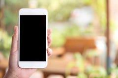 拿着和显示有空白的黑桌面屏幕的手白色巧妙的电话在室外有迷离绿色自然背景 免版税图库摄影