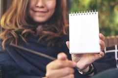 拿着和显示空白的笔记本的一名美丽的亚裔妇女的特写镜头图象在有绿色垂直的庭院的办公室 免版税库存照片