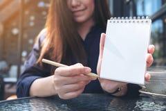 拿着和显示空白的笔记本的一名美丽的亚裔妇女的特写镜头图象 库存图片
