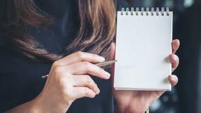 拿着和显示空白的笔记本的妇女在办公室 库存照片