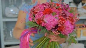 拿着和显示花束的专业卖花人在演播室 影视素材