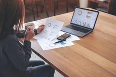 拿着和看企业数据和文件与膝上型计算机的女实业家在桌上,当喝咖啡在办公室时 免版税图库摄影