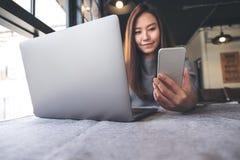 拿着和看手机的一名美丽的亚裔妇女,当使用膝上型计算机在咖啡馆时 库存图片