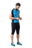 拿着和看手机的循环的球衣和绑腿的年轻运动员 免版税库存照片