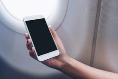 拿着和看有空白的桌面屏幕的手的大模型图象白色巧妙的电话在飞机窗口旁边 免版税库存图片