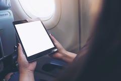 拿着和看有空白的白色桌面屏幕的妇女的大模型图象黑片剂个人计算机在飞机窗口旁边 免版税库存照片