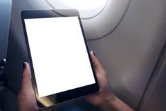 拿着和看有空白的白色桌面屏幕的妇女黑片剂个人计算机在与云彩和天空后面的一个飞机窗口旁边 图库摄影