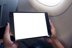 拿着和看有空白的白色桌面屏幕的妇女黑片剂个人计算机在与云彩和天空backgr的一个飞机窗口旁边 免版税库存图片