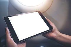 拿着和看有空白的白色桌面屏幕的妇女黑片剂个人计算机在飞机窗口旁边 图库摄影