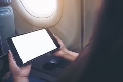 拿着和看有空白的白色桌面屏幕的妇女黑片剂个人计算机在飞机窗口旁边 免版税图库摄影