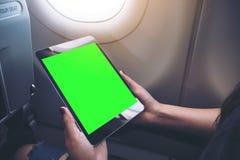 拿着和看有空白的绿色桌面屏幕的妇女的大模型图象黑片剂个人计算机在飞机窗口旁边 库存图片