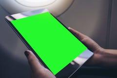 拿着和看有空白的绿色桌面屏幕的妇女黑片剂个人计算机在飞机窗口旁边 免版税库存照片