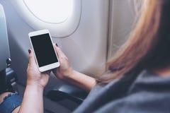 拿着和看有空白的黑桌面屏幕的妇女的大模型图象白色巧妙的电话在飞机窗口旁边 免版税库存图片
