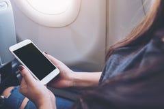 拿着和看有空白的黑桌面屏幕的妇女的大模型图象白色巧妙的电话在飞机窗口旁边 图库摄影