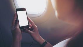 拿着和看有黑白色屏幕的妇女的大模型图象黑巧妙的电话在飞机窗口旁边 免版税库存照片