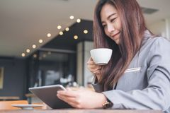 拿着和看片剂个人计算机的亚裔女商人,当喝在现代咖啡馆时的咖啡 免版税库存图片