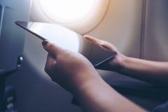 拿着和看黑片剂个人计算机的妇女的特写镜头图象在与云彩和天空的一个飞机窗口旁边 免版税库存照片