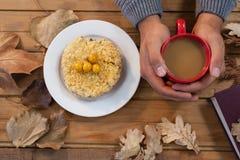 拿着咖啡与早餐的和在桌上的秋叶的人的手 库存照片