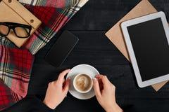 拿着咖啡和使用在一个木桌、技术和通信概念,舱内甲板位置的妇女一种数字式片剂 库存图片