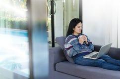 拿着咖啡和使用在沙发的妇女计算机膝上型计算机  免版税图库摄影