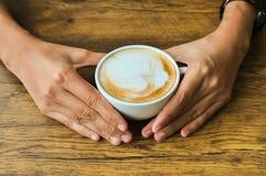 拿着咖啡在土气木桌backg的女性手 免版税库存图片