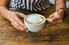 拿着咖啡在土气木桌backg的女性手 免版税库存照片