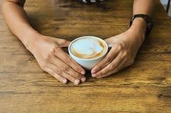 拿着咖啡在土气木桌backg的女性手 库存照片