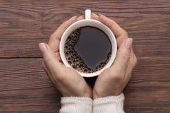 拿着咖啡在土气背景的女性手 库存图片