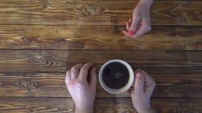 拿着咖啡在手上在木桌上和喝它的人和wooman 股票视频