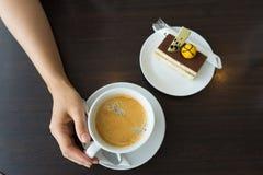 拿着咖啡在木桌上的女性手 库存图片