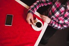 拿着咖啡在桌上的女性手与一张红色桌布, 库存图片