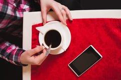 拿着咖啡在桌上的女性手与一张红色桌布, 免版税图库摄影