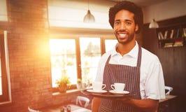 拿着咖啡在盘子的侍者的综合图象 免版税库存图片