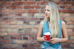 拿着咖啡在砖墙backg的美丽的白肤金发的妇女 免版税图库摄影