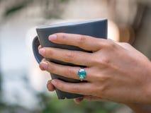 拿着咖啡杯和佩带绿色宝石rin的特写镜头女性手 库存照片