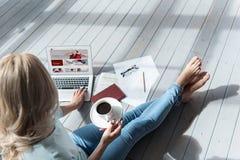拿着咖啡杯和使用膝上型计算机的妇女顶视图 图库摄影