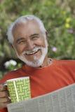 拿着咖啡杯和报纸的愉快的老人 免版税库存照片