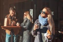 拿着咖啡杯和新月形面包和看与微笑的太阳镜的美丽的年轻白肤金发的妇女太阳,当站立室外时 免版税库存照片