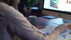 拿着咖啡杯和研究计算机的女性手在书桌后面视图 影视素材
